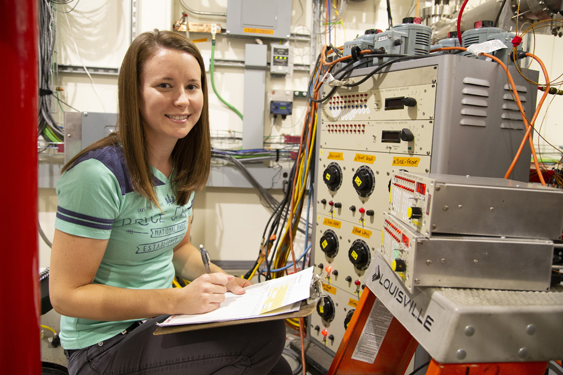 Katie Moring inspecting machinery at the Cornell high Energy Synchrotron Source.