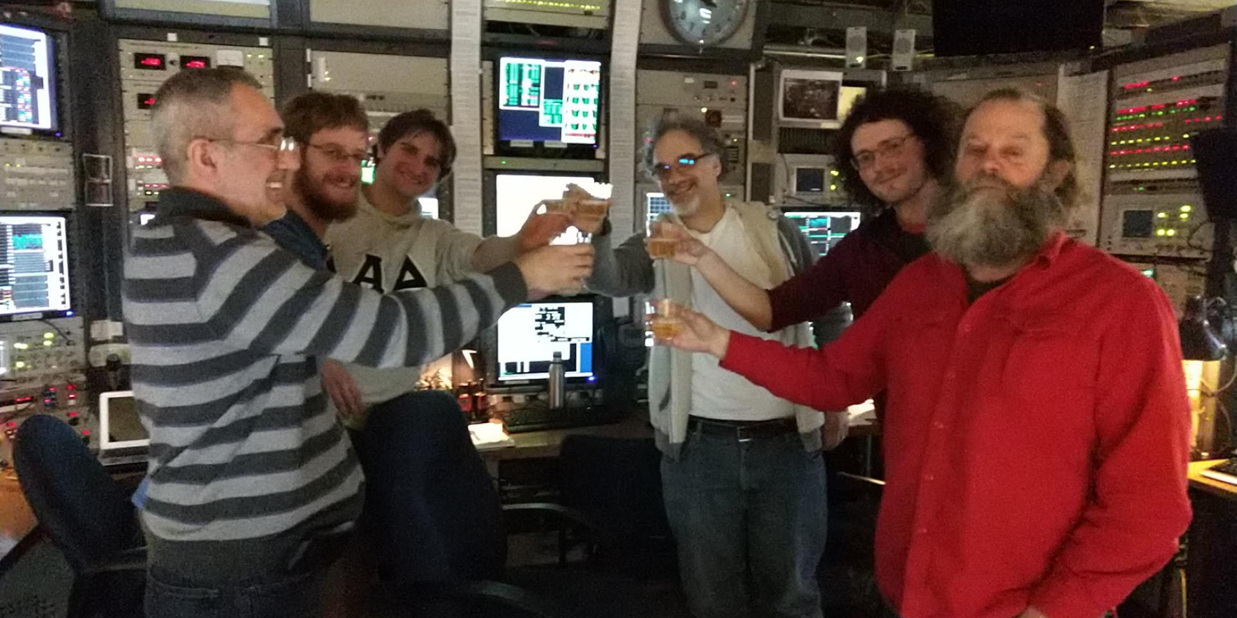 Team celebrates first turn of positrons on March 6, 2019
